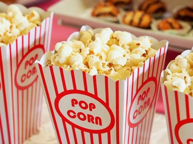 Rot-weiß gestreifte Popcorntüte mit Popcorn drin