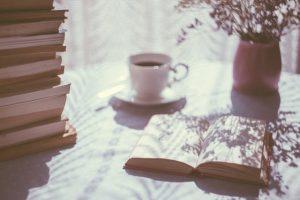 geöffnetes Buch neben Bücherstapel und Kaffeetasse