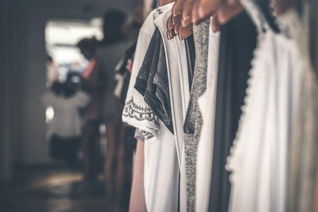 Weiße und dunkle Kleidung auf Kleiderbügeln auf Kleiderstange