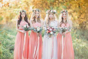 Braut neben Brautjungfern mit Blumen im Tageslicht