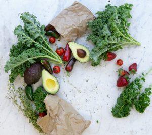 Gemüseeinkauf: Papiertüten und Avocados, Grünkohl, Erdbeeren, Tomate