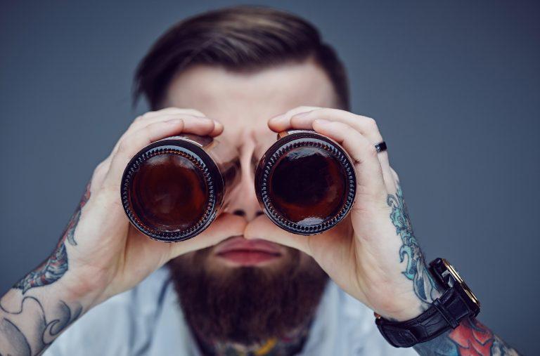 Bearded hipster man holding beer bottles like binocular, Symbolbild Vegane Getränke