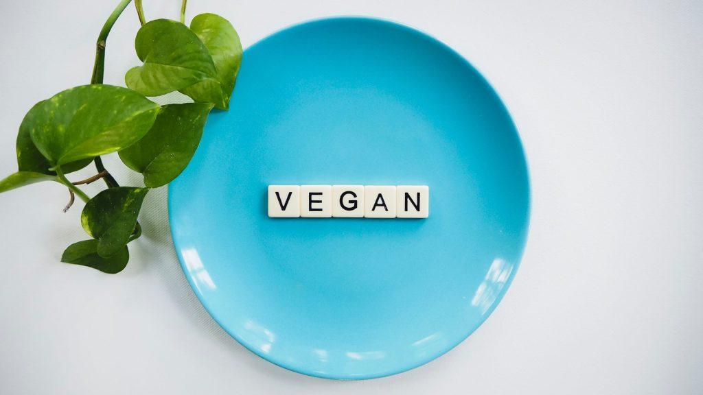 Schriftzug vegan auf blauem Teller