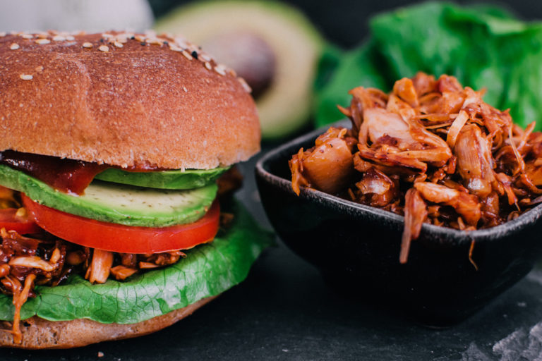 Jackfruit Burger auf Schiefer-Brett neben Tomaten