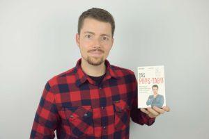 """Jan Rein hält sein Buch """"Das Pups-Tabu"""" in die Kamera"""