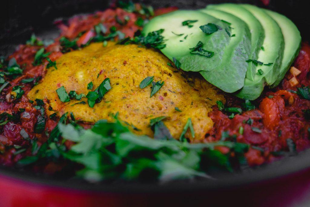Vegane Shakshuka mit Ei-Ersatz und Avocadoscheiben