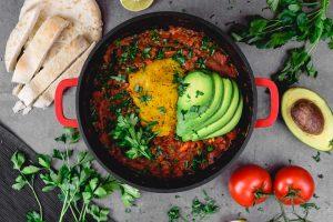 Shakshuka in einem kleinen Topf veganes Rezept mit Avocado, Tomaten, Brot
