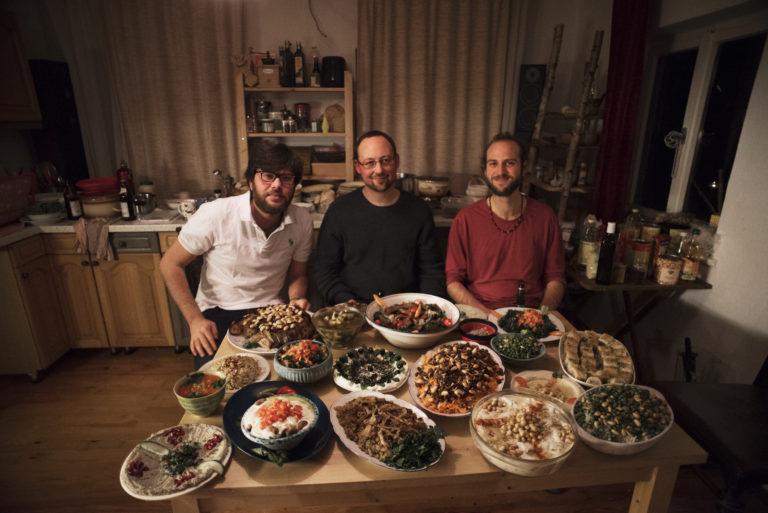 Die WG-Bewohner sitzen am Tisch mit mehreren arabischen Speisen wie Baba Ghanoush
