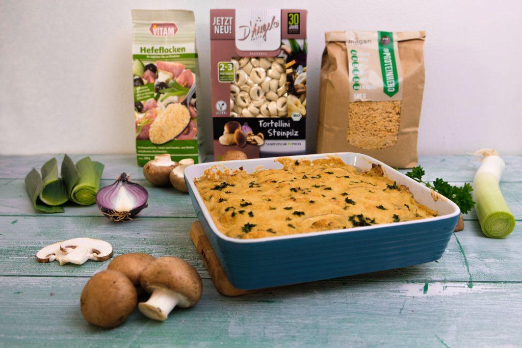 Tortellini-Auflauf neben Pilzen und Produkten