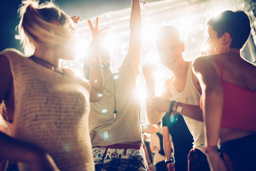 Tanzende Menschen im Gegenlicht auf Festival