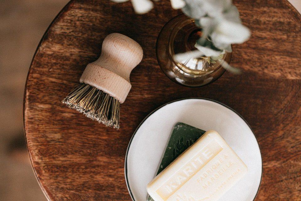 Rasierpinsel mit Holzgriff neben Seife auf Holztisch