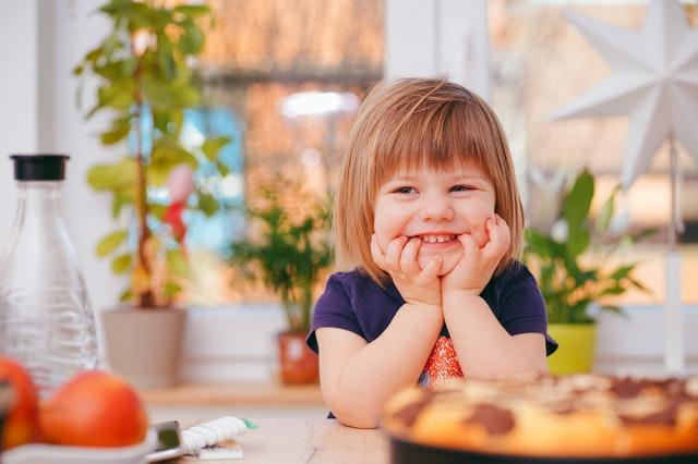 Kind am Esstisch, das in die Kamera lacht