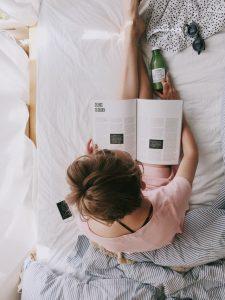 Frau in einem rosa Kleid sitzt auf dem Bett und liest