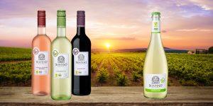 3 Flaschen veganer Wein neben Sektflasche