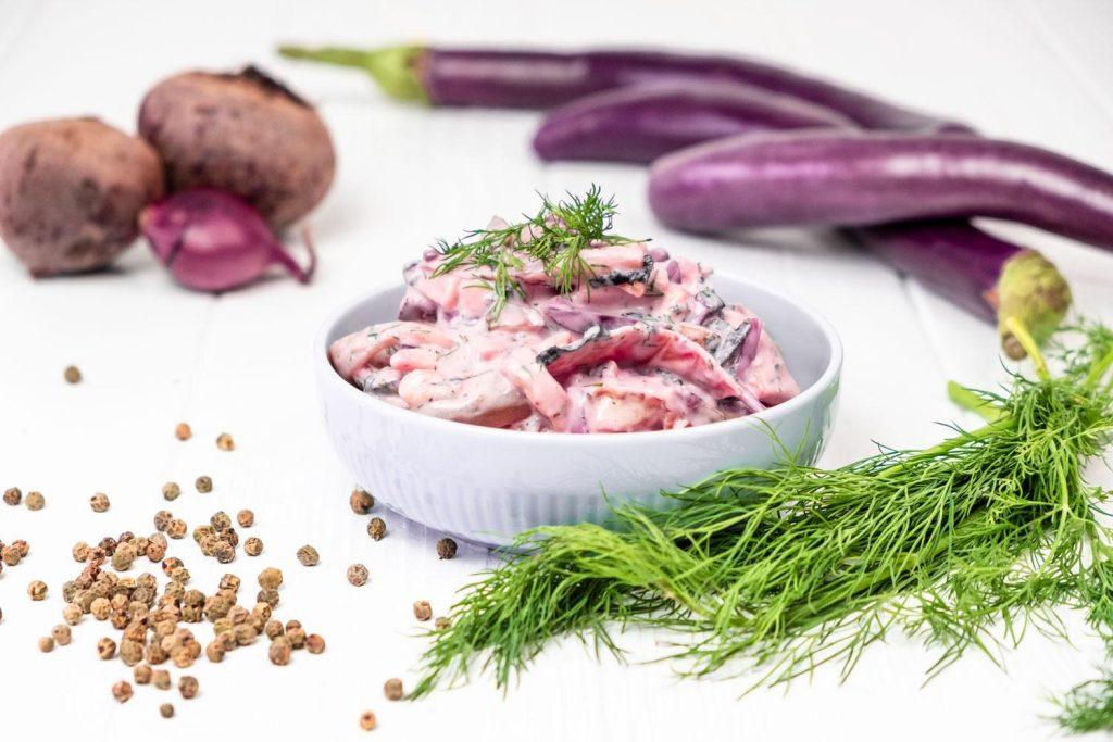 Veganer Heringssalat in weißer Schale neben Auberginen und Dill