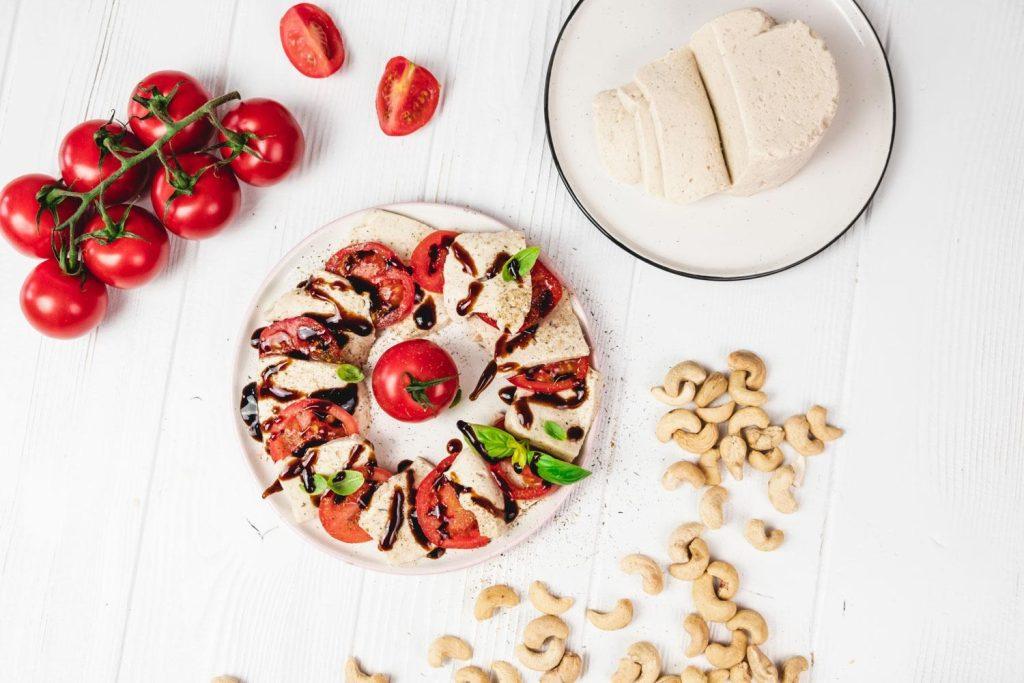 Tomate-Mozzarella-Platte von oben neben Cashews und Tomaten