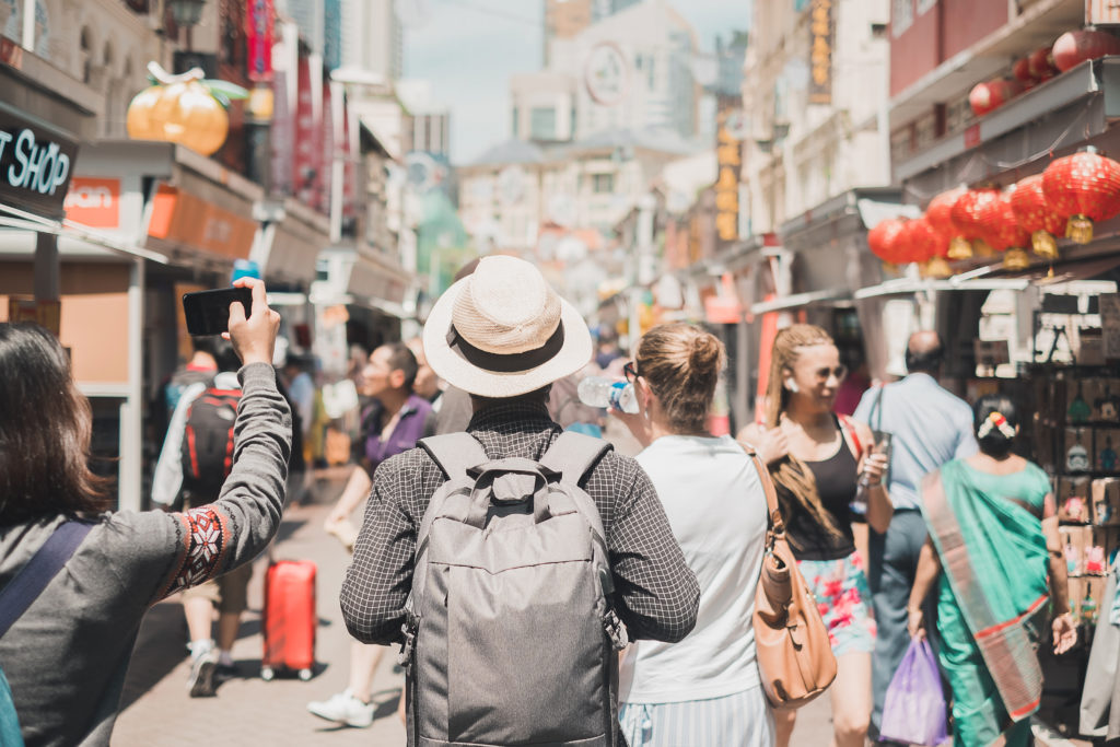 Young man traveling with backpack and hat, happy Solo traveler walking at Chinatown street market in Singapore. landmark and popular for tourist attractions. Southeast Asia Travel concept