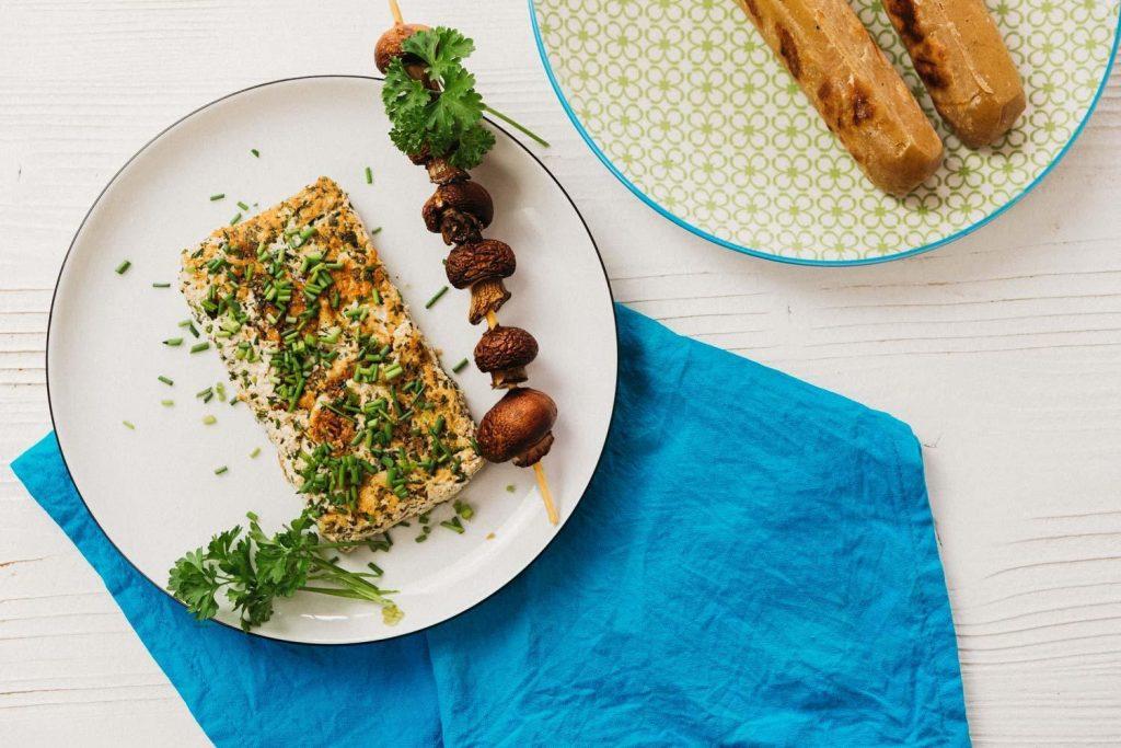 Veganer Grillkäse neben Pilzspieß auf weißem Teller