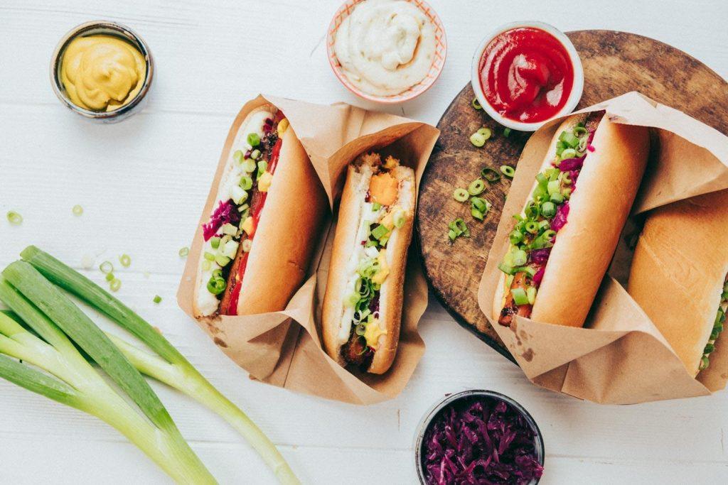 Vegane Hotdogs mit Ketchup, Mayonnaise, Senf, Lauchzwiebeln auf einem Holzbrett