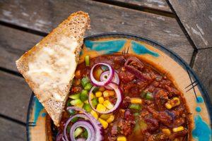 Veganes Chili sin carne in bunter Schüssel mit Brot