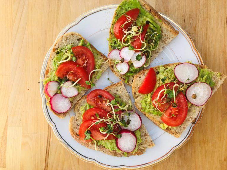 Vier halbe Brote mit Avocado, Tomate, Redieschen und Sprossen