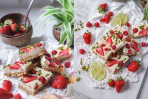 Vegane Yoghurt Bars mit Erdbeeren, Himbeeren und Limette. Zusammen angerichtet auf einem weißen Tuch.