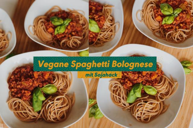 Spaghetti Bolognese vegan angerichtet auf weißen Tellern und einem Holzbrett