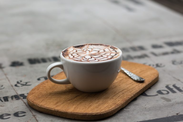 Cappuccino in weißer Tasse auf Holzbrett