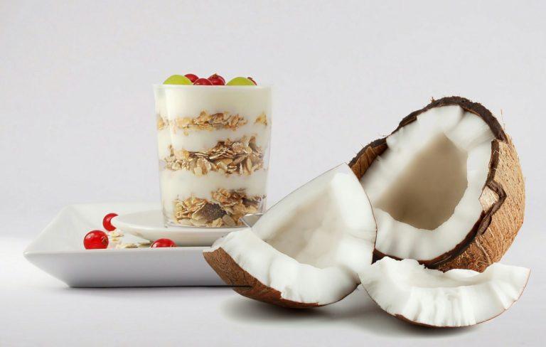 Kokosnuss neben Glas mit Müsli, Joghurt und Obst