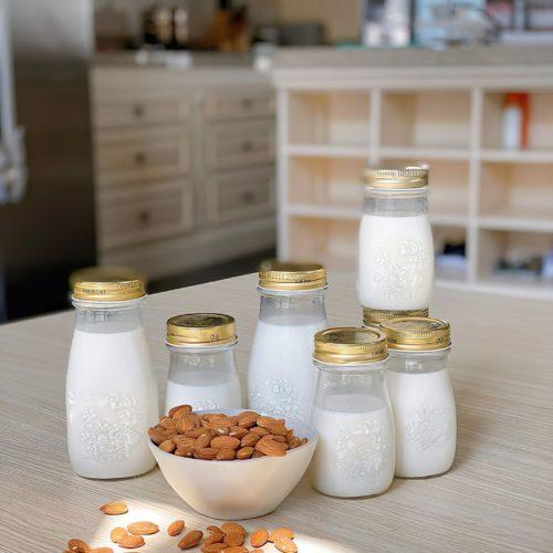Mandeln in einer weißen Schale neben Glasflaschen mit Mandelmilch
