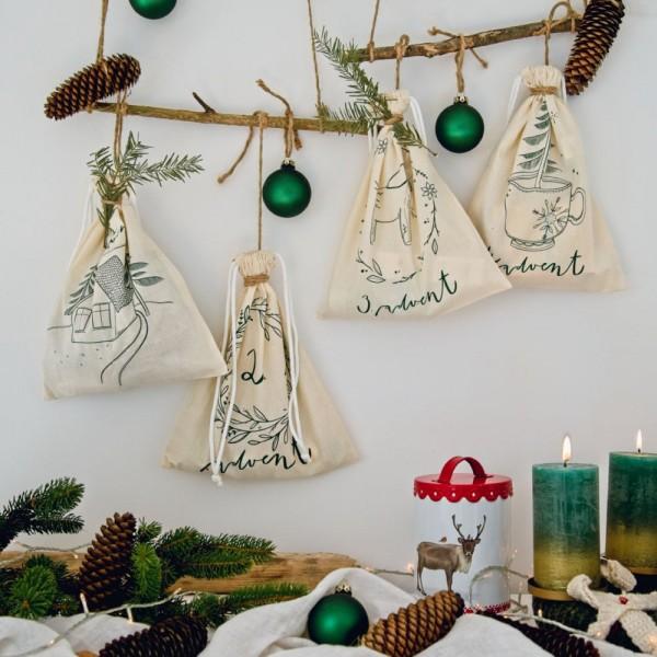 Abbildung des veganen Beauty Adventskalenders: Vier gefüllte Säckchen, die an einem Ast hjängen zusammen mit grünen Baumschmuck-Kugeln