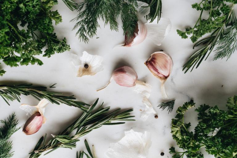 Verschiedene Kräuter und Knoblauchzehen auf weißem Untergrund als Symbolbild für die Zutaten zum Kräuterbutter-Rezept