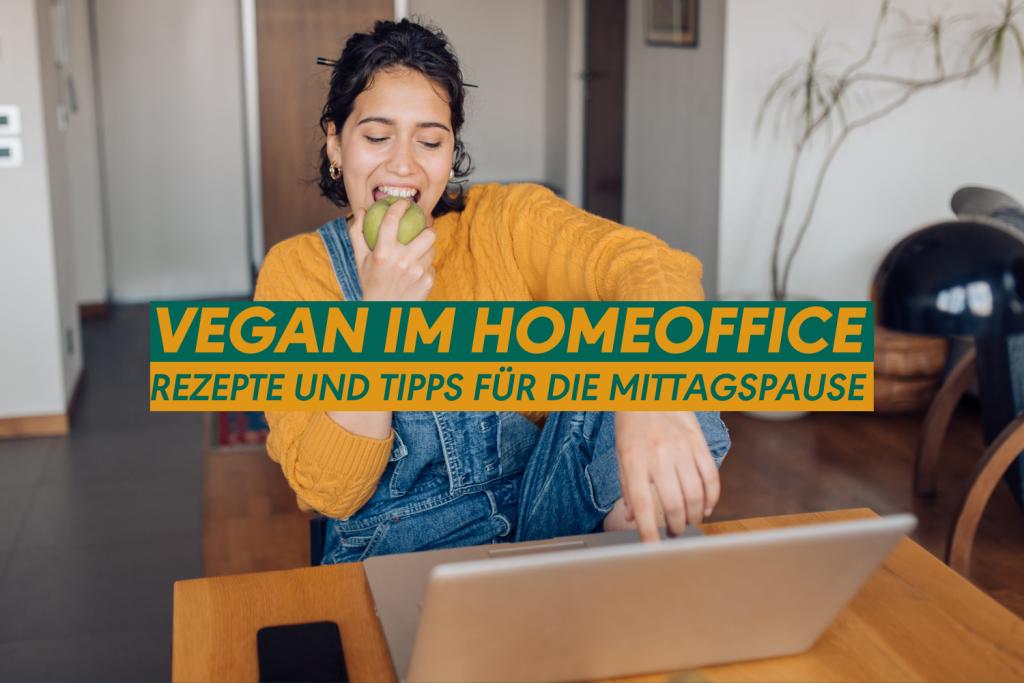 Frau isst einen Apfel vor dem Laptop im Homeoffice