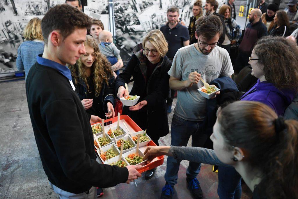 Mensch reicht anderen Menschen vegane Probierportionen auf der VeggieWorld Berlin 2020