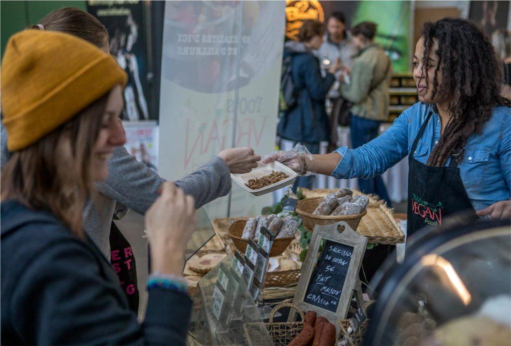 Ausstellerin reicht Kostproba an Besucher auf der VeggieWorld Brüssel 2018
