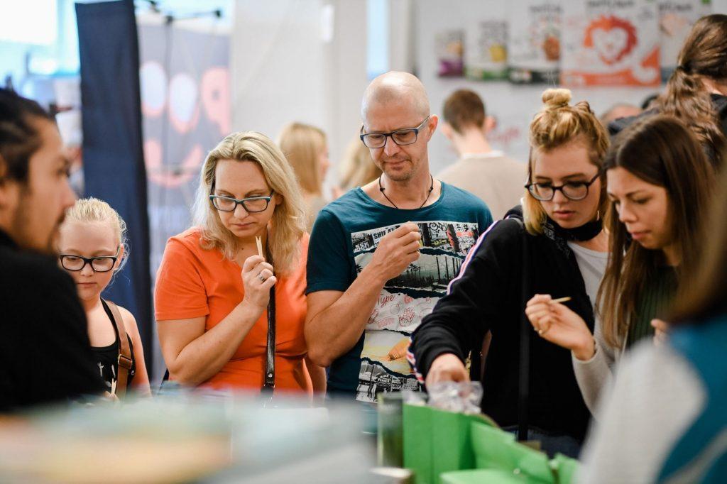 Besucher:innen probieren vegane Produkte an einem Messestand auf der VeggieWorld München 2018