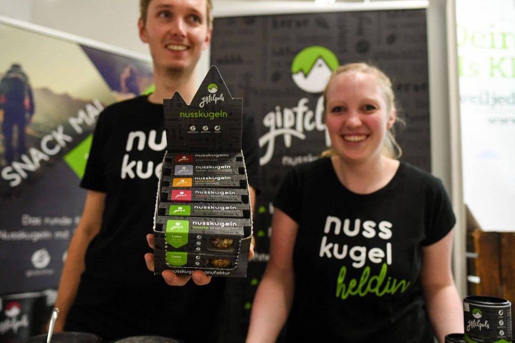 Zwei Aussteller:innen auf der VeggieWorld München 2019 zeigen vegane Riegel in die Kamera