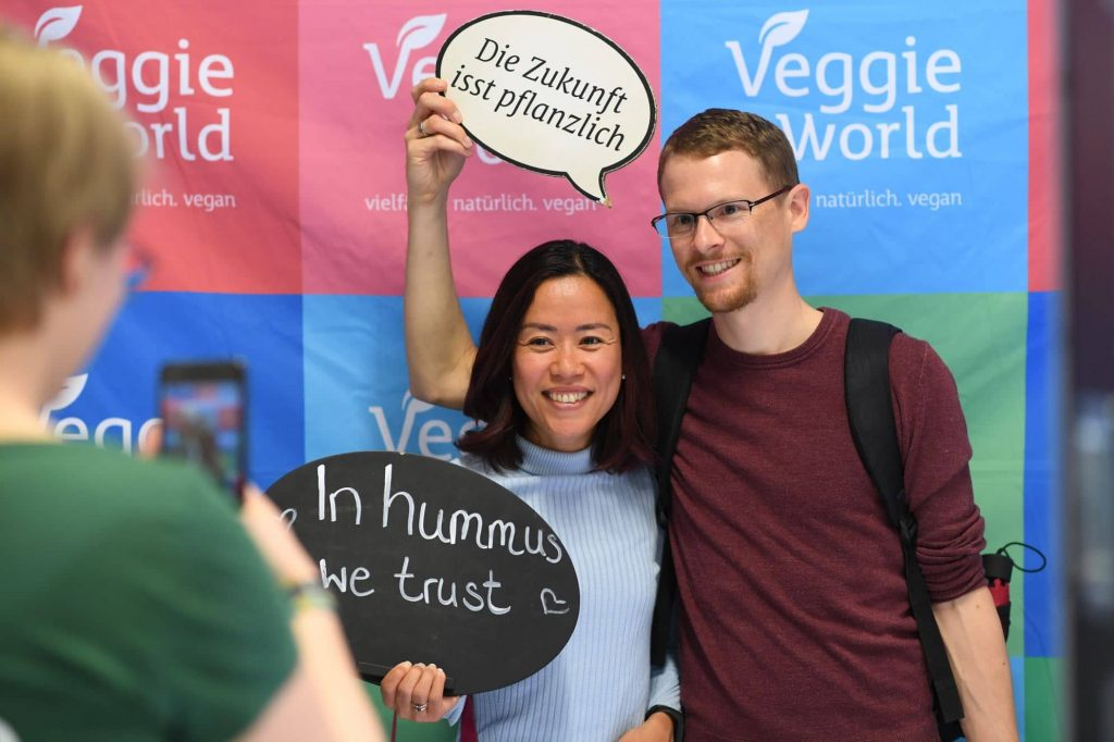 Zwei Besucher der VeggieWorld München machen ein Foto an der VeggieWorld Fotowand