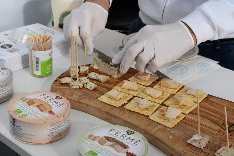 Nahaufnahme von zwei Händen in weißen Handschuhen, die veganen Käse auf Cracker auf einem Holzbrett anrichtet