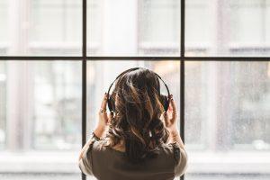Person mit Kopfhörern, die vor einem Fenster steht als Symbolbild für das Artikelthema vegane Podcasts