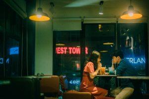 Zwei Personen, die in einem Café sitzen und Getränke zu sich nehmen, draußen ist es dunkel
