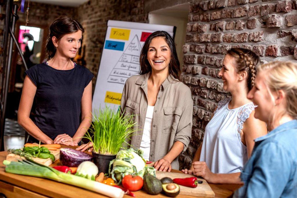 Vier Personen in einem Workshop der Weiterbildung Vegane Ernährungsberatung stehen an einem Tisch mit Gemüse neben Flipchart