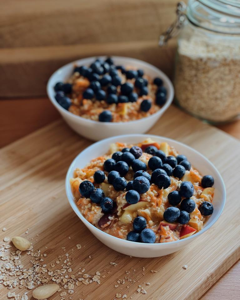 """Rezeptbild zu """"Porridge Grundrezept"""": Haferbrei mit Blaubeeren in weißer Schale auf Holzbrett"""