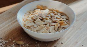 Veganes Mandel-Porridge in weißer Schale auf Holzbrett