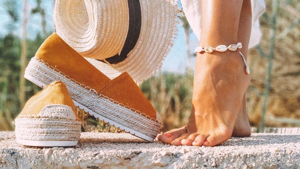 Vegane Sommerschuhe neben Füßen und Strohhut