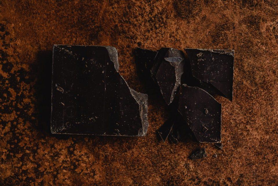 Zerbrochene Schokolade auf brauner Oberfläche