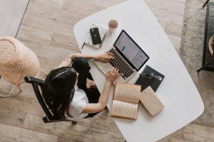 Frau am Schreibtisch von oben fotografiert als Symbolbild für einen Menschen der für das Studium vegane Ernährungsberatung lernt