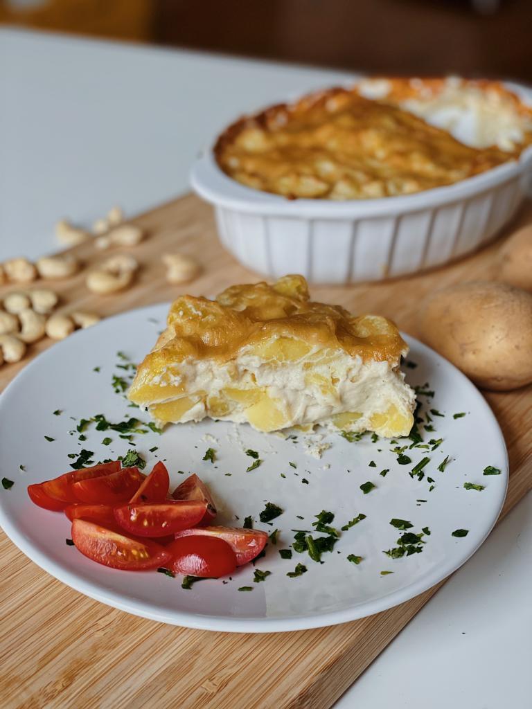 Kartoffelgratin vegan in weißer Auflaufform auf Holzbrett neben Cashews und Kartoffeln